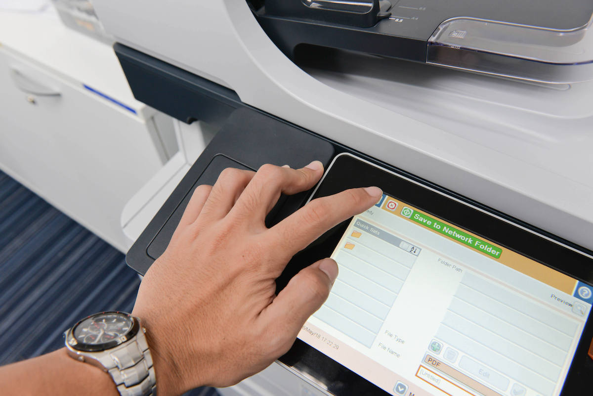 Employee using a digital printer office copy machine