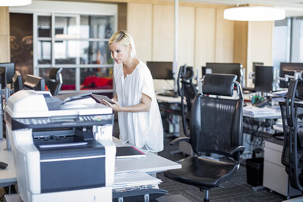 Image description: Woman holding a tablet leans over a multi-function printer. She is in a computer lab.