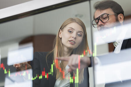 Image of businesswoman and businessman talking profit on a futuristic display