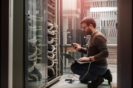 IT professional kneeling in front of a data center performing diagnostics on his laptop.