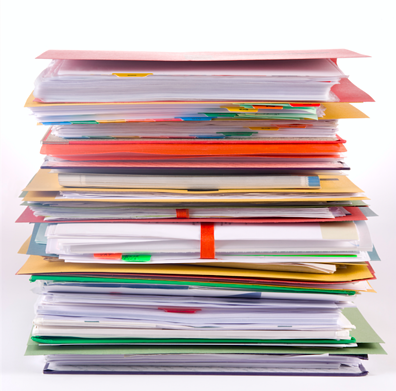 Image description: a stack of file folders filled with paper and multi-colored tabs