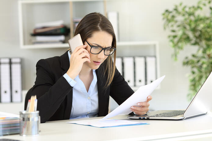 Business woman on a cell phone with a laptop open looking at a piece of paper.