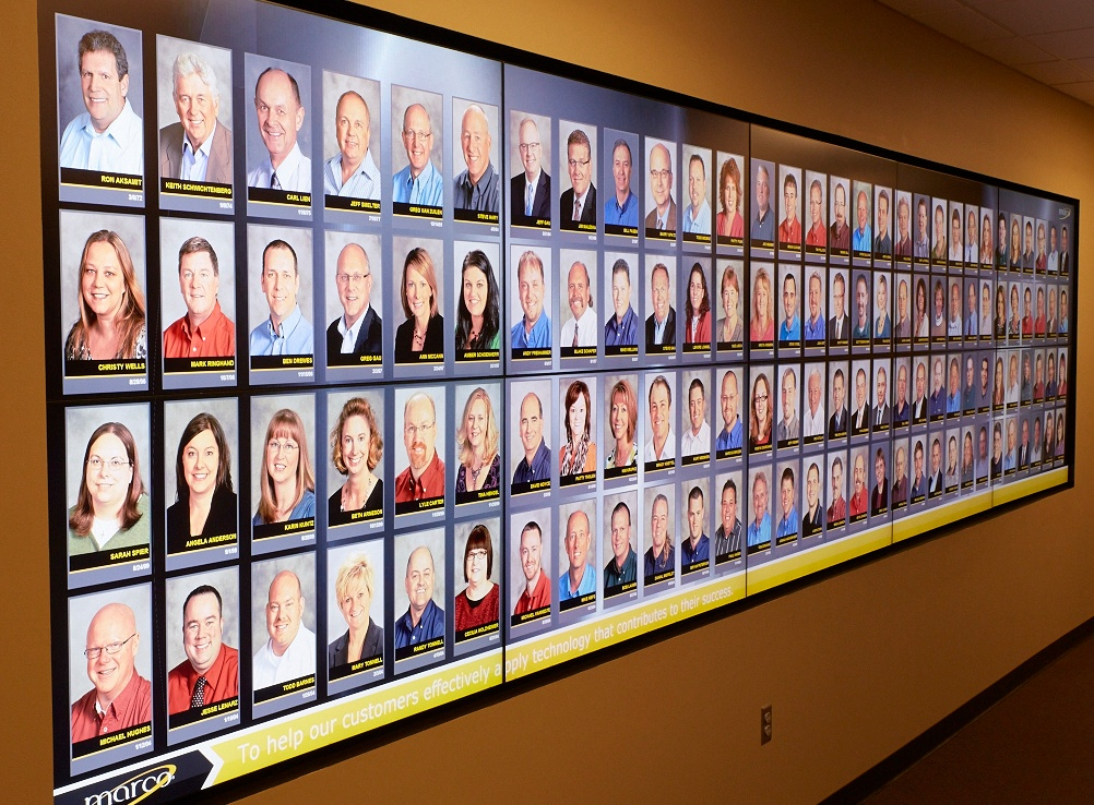 Image description: photo of Marco's video wall from Marco HQ in St. Cloud, MN featuring employee headshots