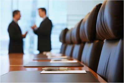 Image description: Boardroom with chairs, folders, pens and two blurred individuals standing in the foreground.