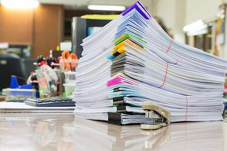 Image description: A stack of bound papers with multi-colored clips and binders sitting atop a desk with a miniature staple in the foreground. Behind the papers, there are numerous other office supplies, including a calculator, scissors, cups filled with pens and a tape dispenser.