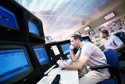 an IT employee watching various monitors to assess network hardware