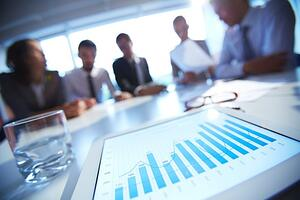 Image of people in a board room reviewing statistics