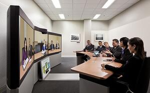 Image description: a rounded board table in a video conferencing room facing a screen depicting another team at a similar table that is conferencing in with the use of telepresence.