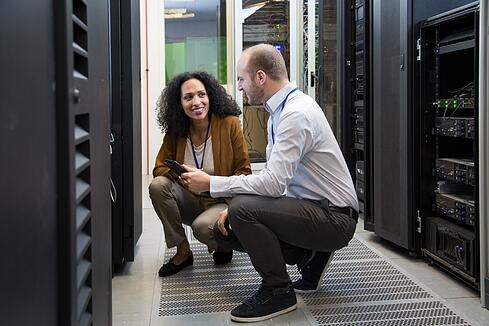 Image description: A woman and a man crouching in front of data center technology making direct eye contact and smiling.