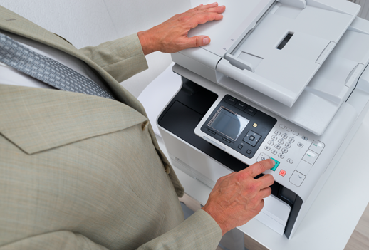 Image Description: Man in a beige suit standing near a printer with one hand on top of the device and the index finger of the other hand poised to press a green button, which will start the print job.